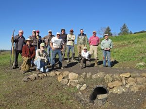 Volunteers pose over the culvert they installed for a new path into Trione-Annadel State Park. (Photo by Robert Starkey)