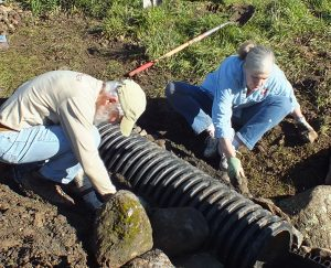 Jim Mayer and Sue Harrisoin anchor the culvert pipe. (Photo by John Williston)